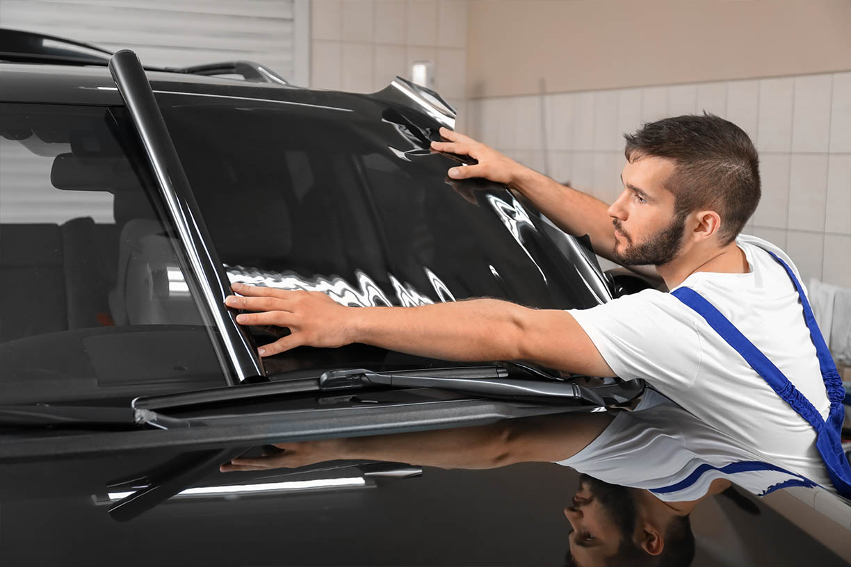 technician applying window film on black cars car windscreen